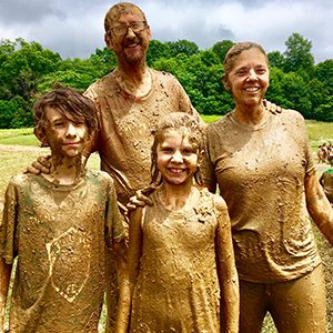 a family covered in mud