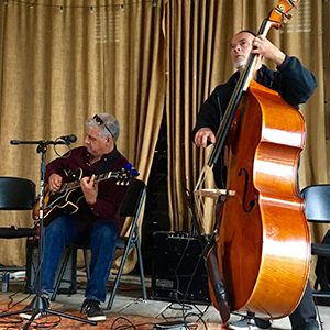 A man playing a guitar and another playing a large cello