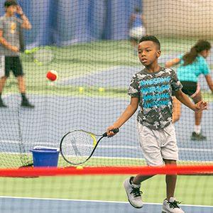 A child hitting a tennis ball