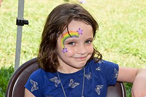 Young girl with face painting design of a rainbow
