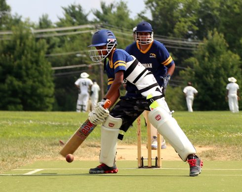 Two men playing cricket