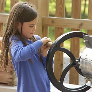 Young girl in blue shirt turning the wheel of a cider press