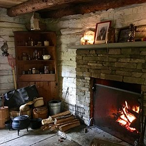 Fireplace with fire, antique tools and corner cupboard in the Harper Cabin