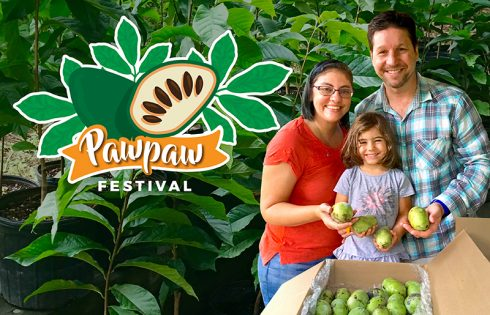 Family standing in front of pawpaw trees holding fruit