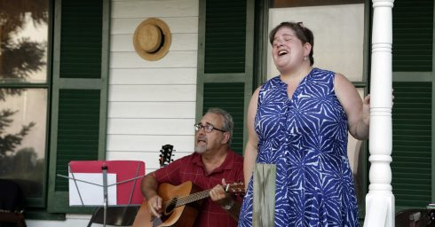 A woman singing on a porch with my man playing guitar.