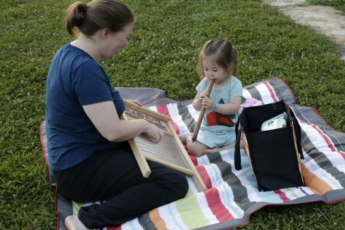 A mom and daughter play instruments
