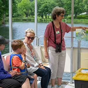 Young boy in a lifevest with his grnadmother with Pontoon Boat Tour Guide explaining the water edge