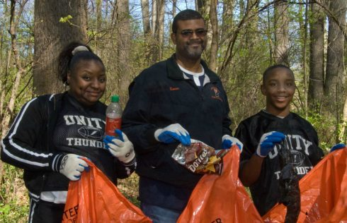 A family holding volunteer pick up bags