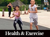 Two young girls running together with a black bar at the bottom that says Health and Exercise