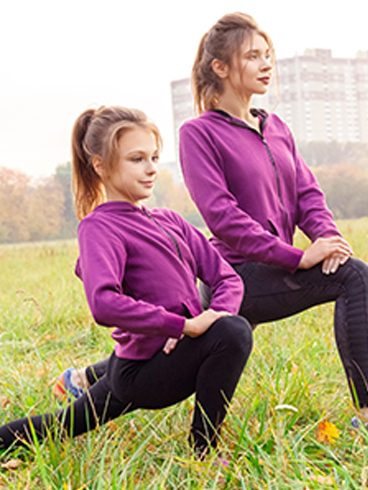 Young girl and her mother, dressed alike in purple sweatshirt and black workout pants, do lunge exercises outdoors