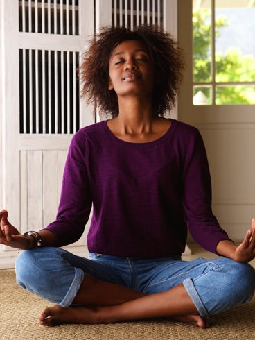 African American woman sitting in her living room meditating