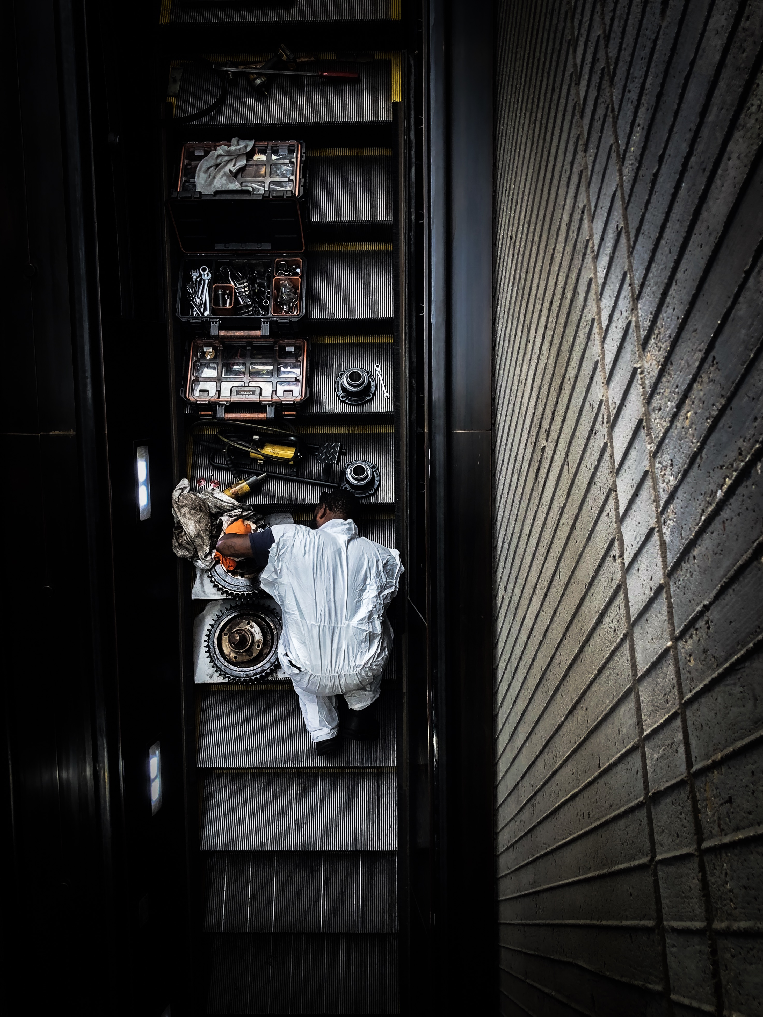 """Photograph of the """"Working Man"""" is a portrait of one man's intricate, detailed, and meticulous handling of the mechanical work and care that goes into the engineering of the escalator."""