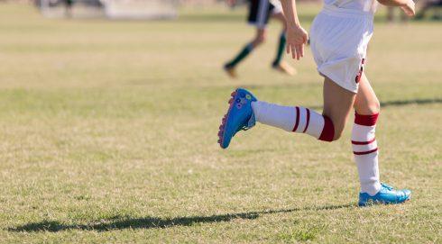 A soccer player's feet running on a fiekd