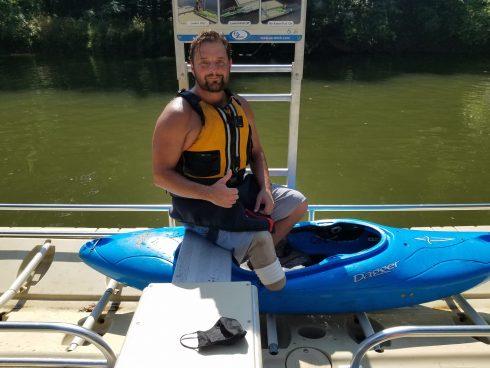 Man sitting next to kayak