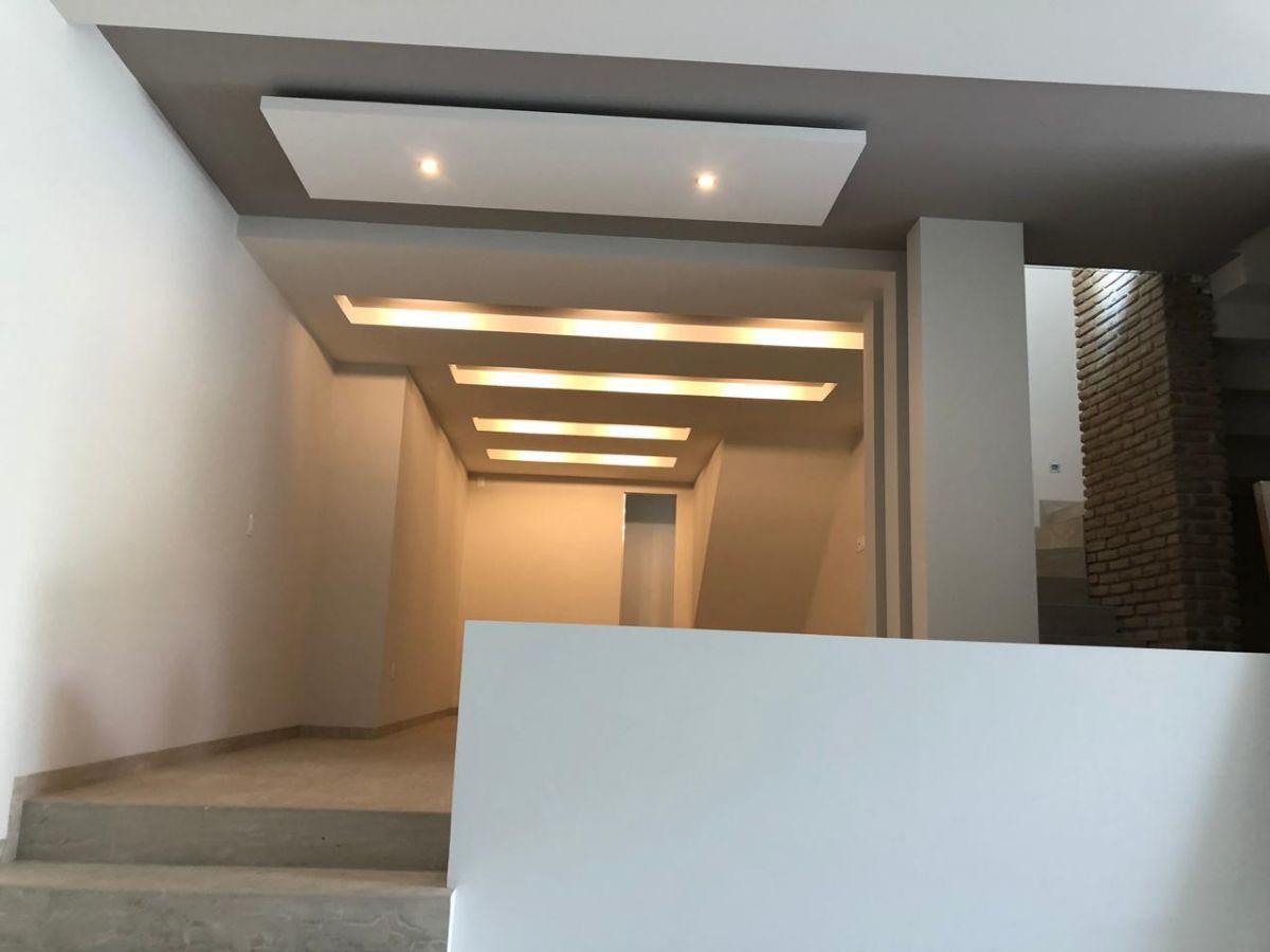19 de 41: Amplio family room con plafones y luces indirectas.