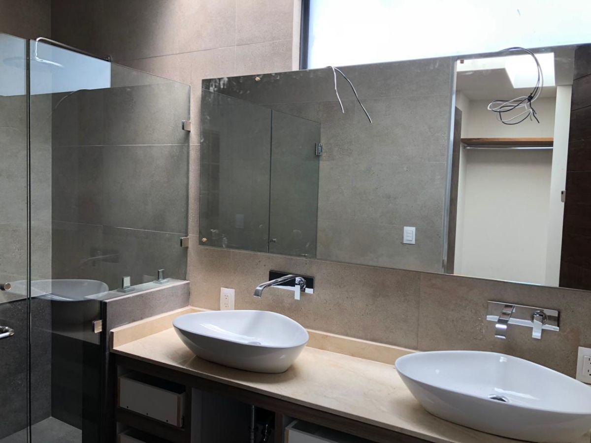 28 de 41: Área de baño con doble tarja, regadera con acabados de lujo