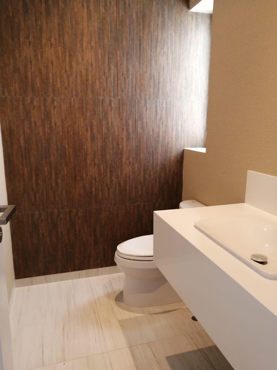 22 de 36: Fino baño de visitas con pared enchapada y empapelada