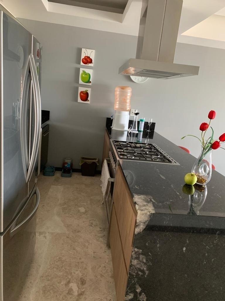 7 de 25: Cocina con barra de granito, estufa y campana, torre hornos