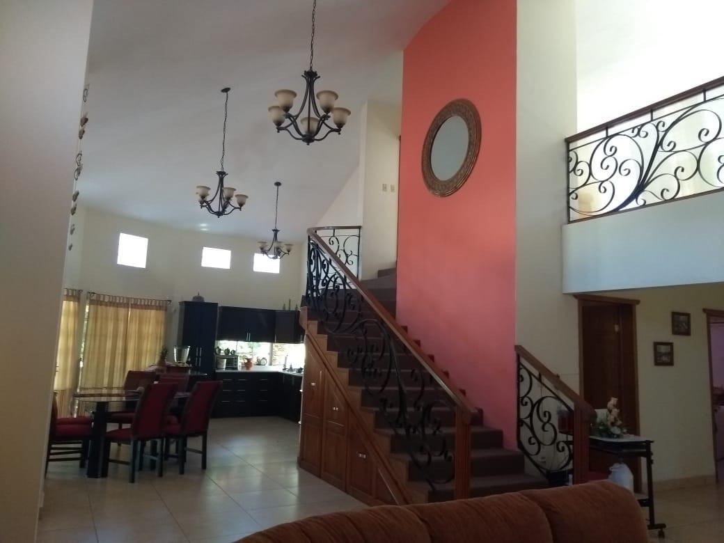 1 de 21: Vista desde sala al área de comedor, cocina y escaleras