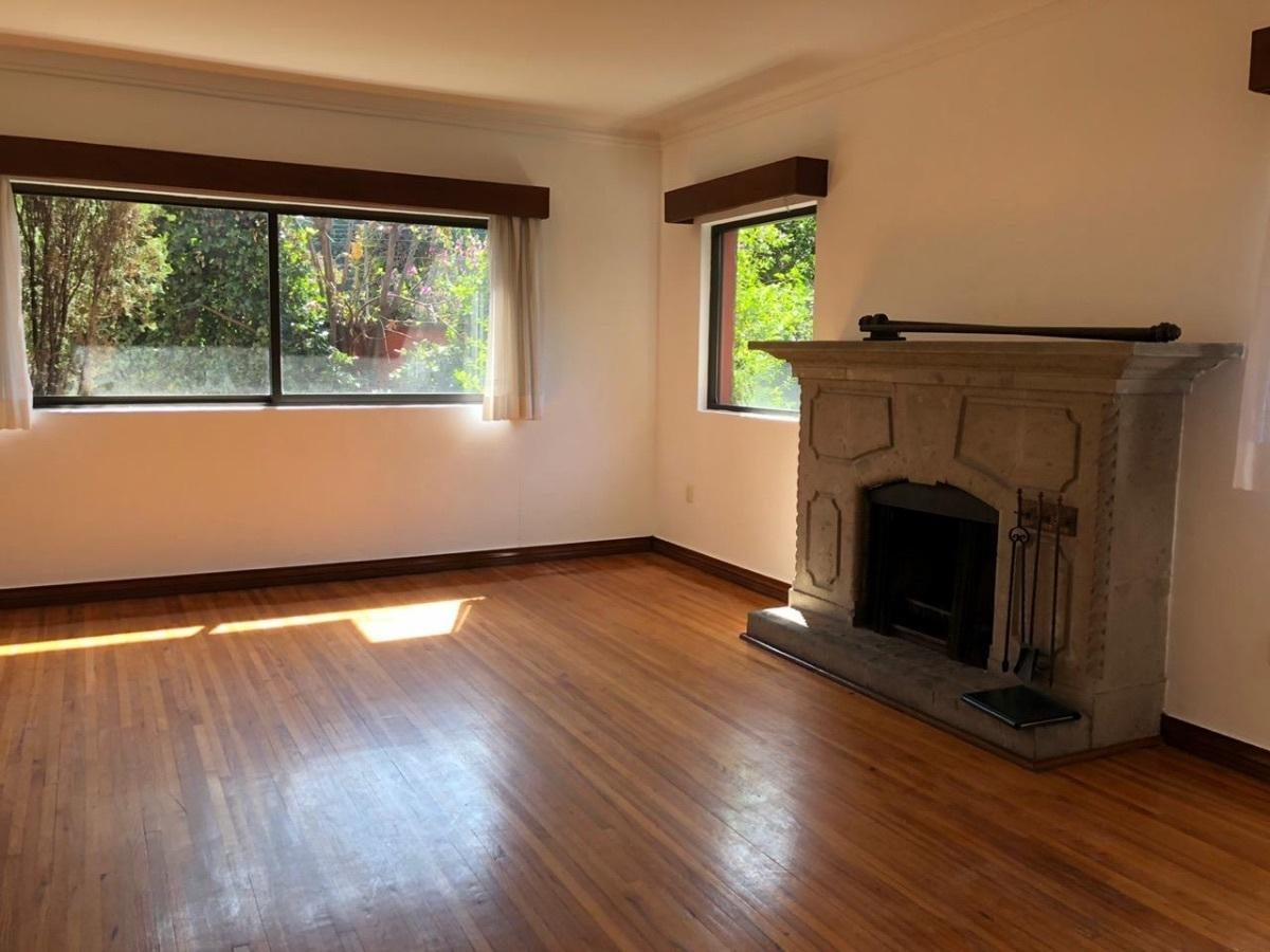 7 de 12: Sala con chimenea y piso de madera natural