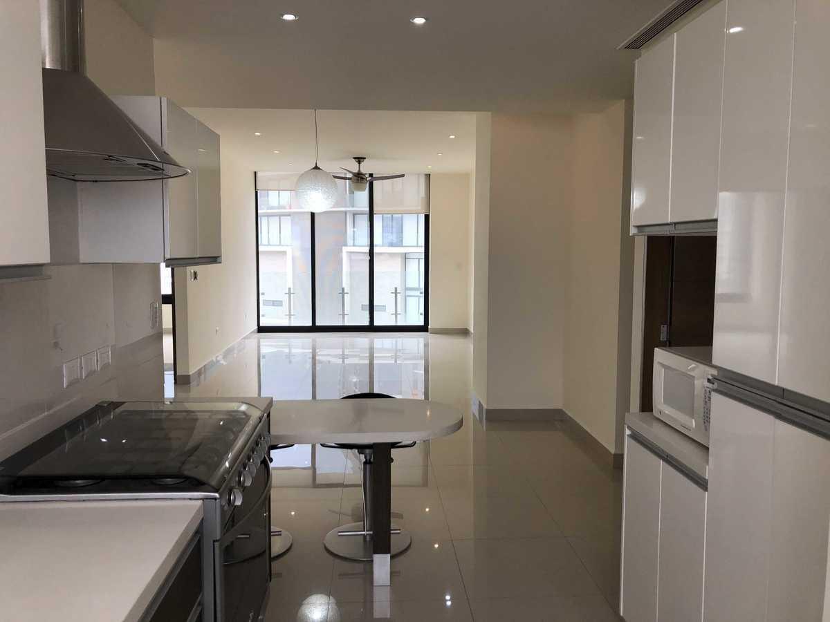 4 de 27: Cocina integral con barra de Corian, sala comedor y balcón