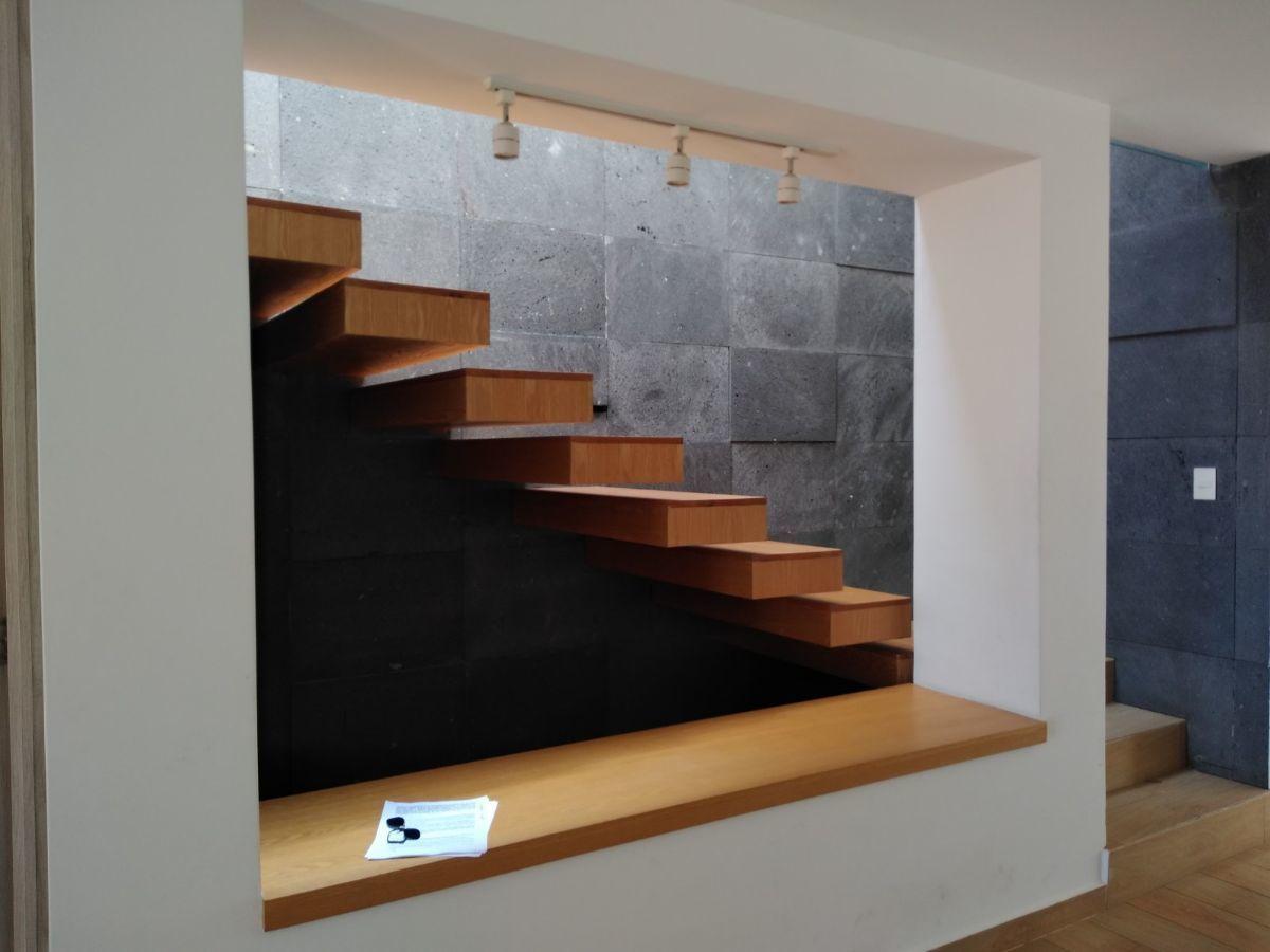 5 de 13: Escalera de madera y pared de piedra.