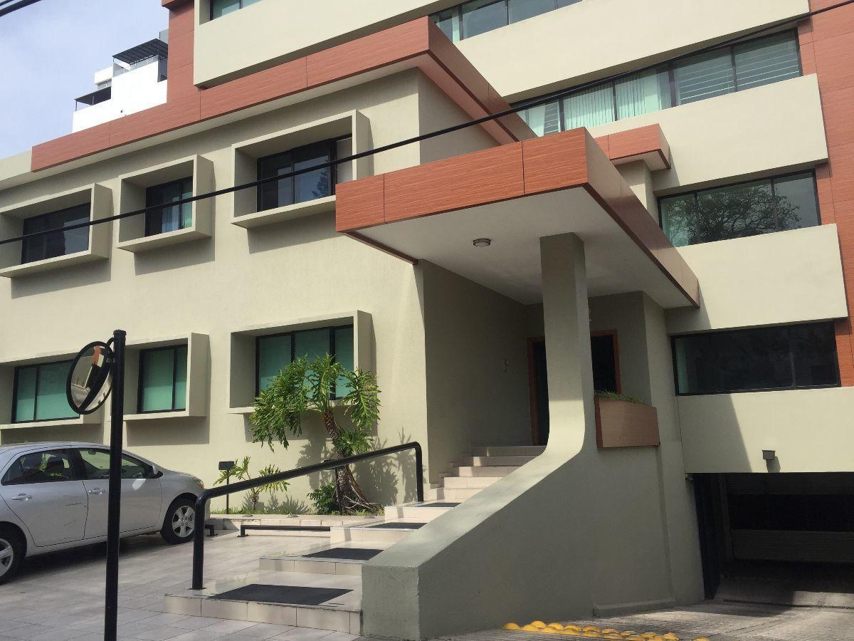 6 de 10: frente del edificio con algunos lugares de estacionamiento