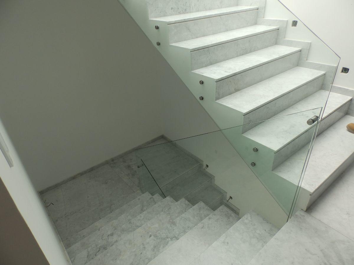 18 de 21: Escalera de mármol y barandales de vidrio.