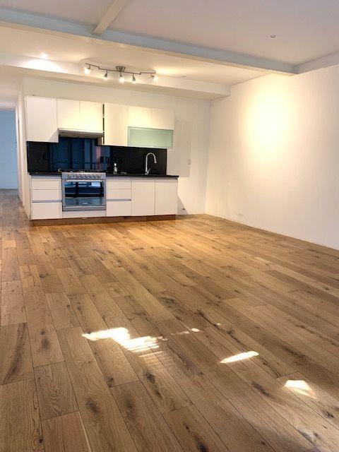 3 de 18: Cocina abierta con sala-comedor y pisos de madera