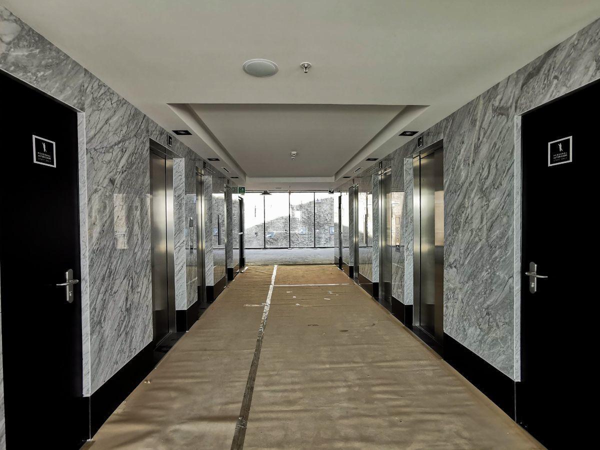9 de 19: Pasillo de oficinas con baños y elevadores