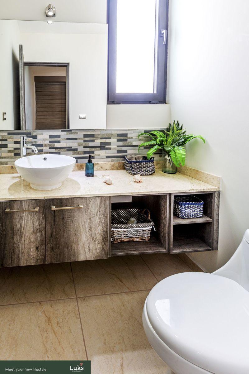 7 de 17: Medio baño de visitas con muebles y espejos e iluminación.