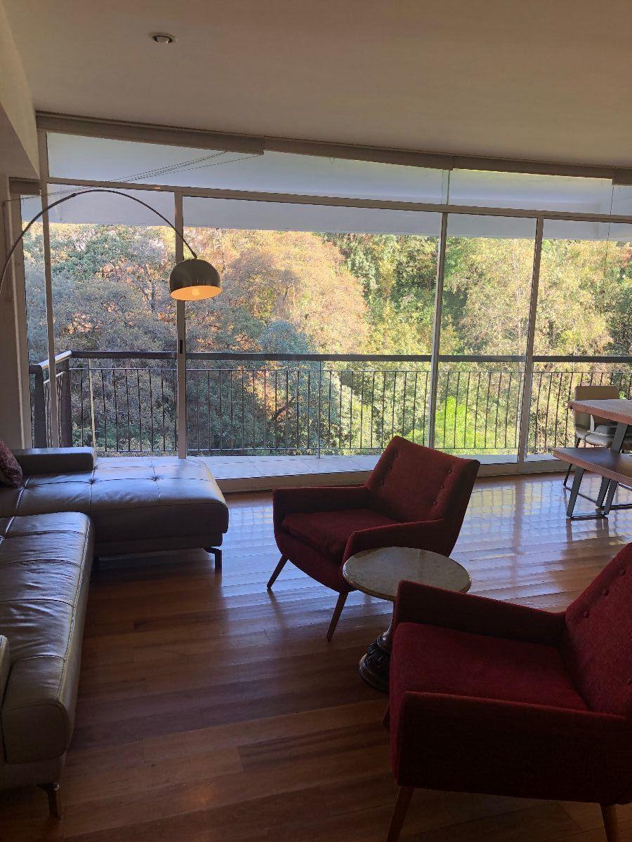 2 de 34: Sala con pisos de madera y vista arbolada
