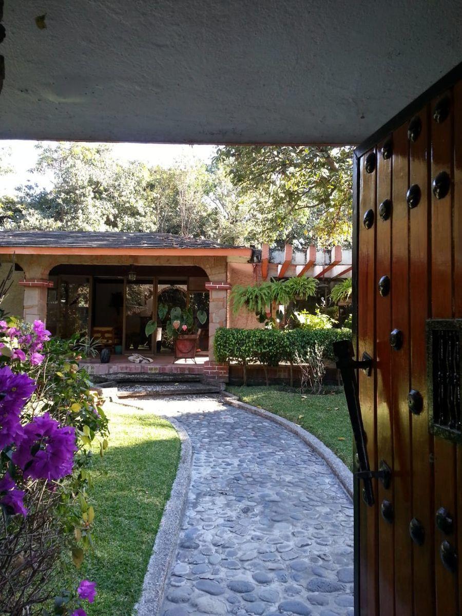 1 de 16: Entrada a la casa  con camino de piedra y puerta de madera.