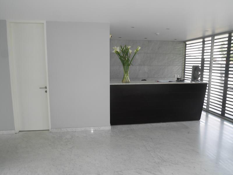 26 de 31: Elegante Lobby con pisos en mármol y jardinera interior