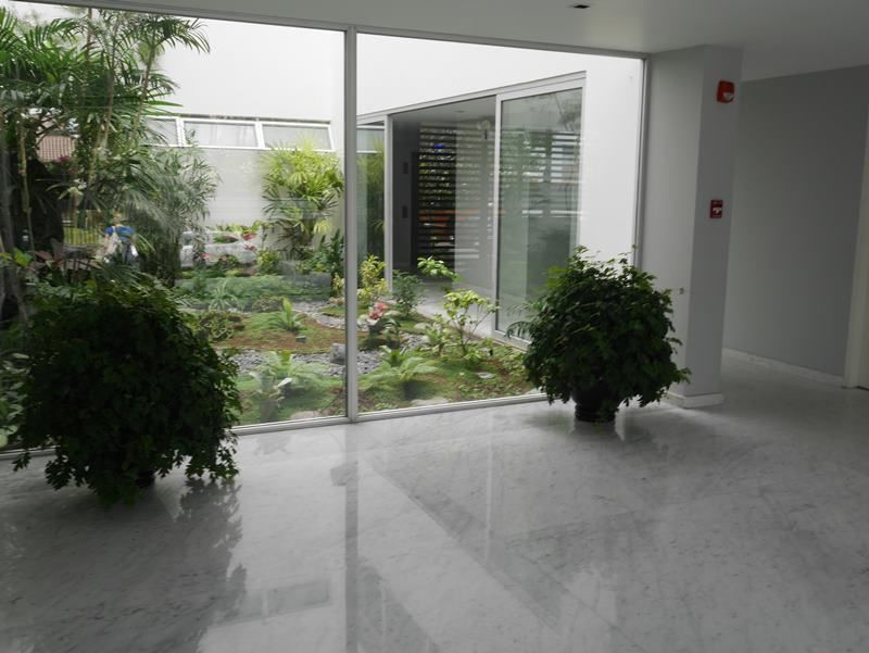 27 de 31: Elegante Lobby con pisos en mármol y jardinera interior