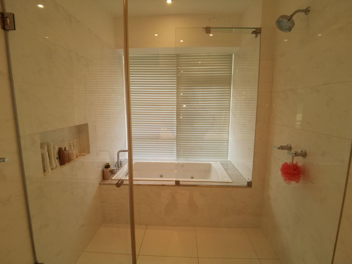 26 de 41: Baño principal elegante y neutro con jacuzzi y luz natural