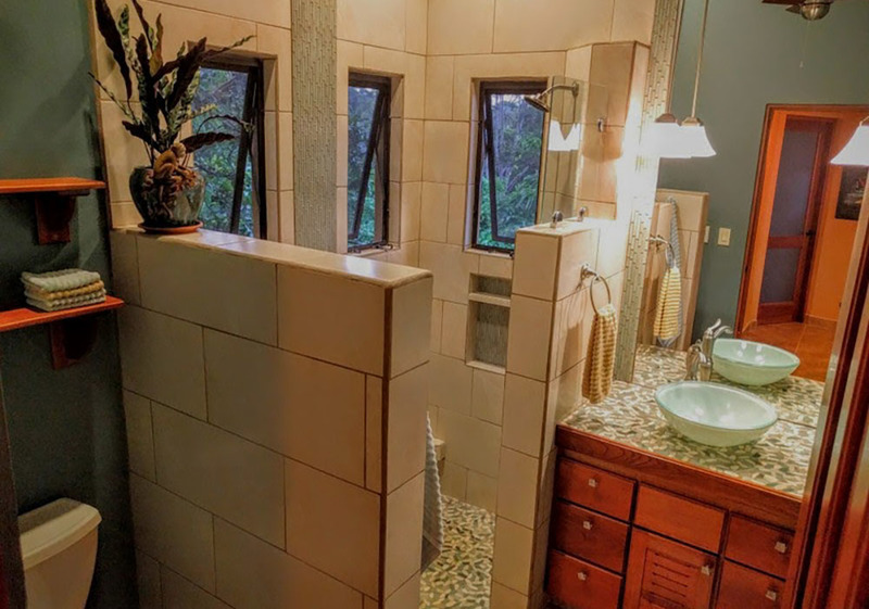 8 of 18: Bathroom with glass sink and Delta fixtures.