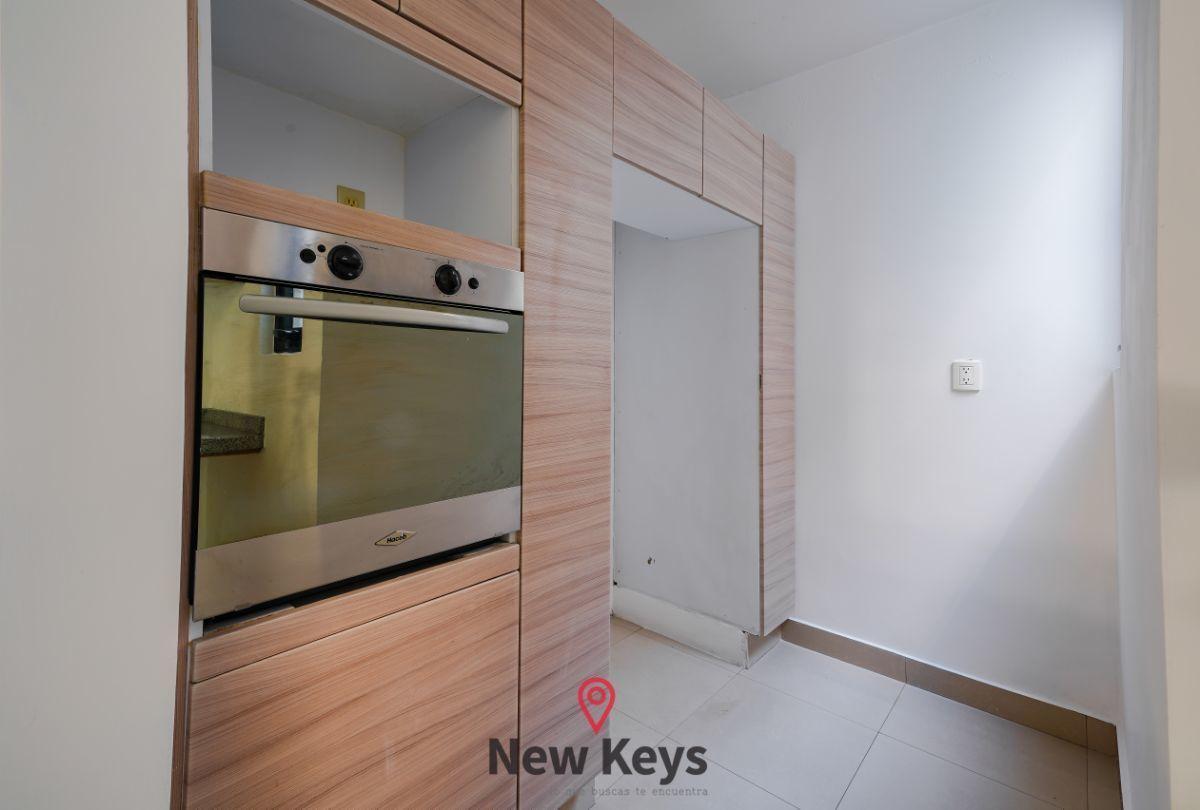 4 de 24: Zona de refrigerador y horno al interior de la cocina