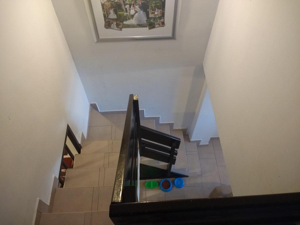 9 de 12: Escaleras de piso cerámico con barandal de madera.