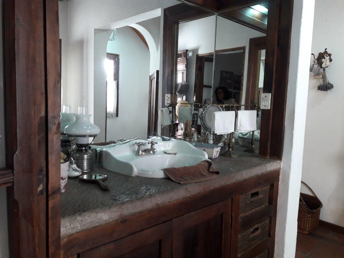 26 de 48: Lavabo suite 1 con plancha de cantera y muebles de madera