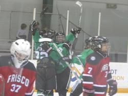 Dragons Varsity teammates celebrate the goal by Saunders Penn (#22) against Weston Walker of Frisco