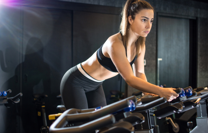 Woman exercises on stationary bike, Peloton IPO looms.