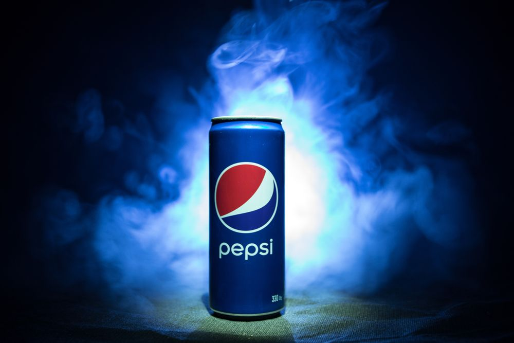 A blue can of Pepsi against a beautiful hazy and cloudy black and blue background | Investment U