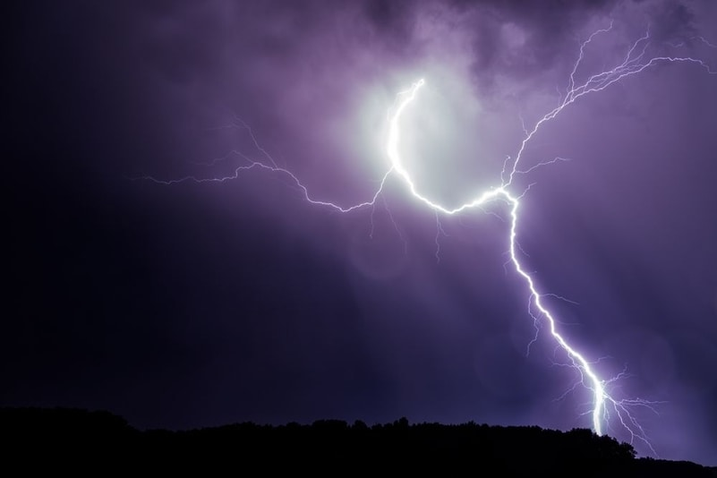 "Lightning strikes against a deep purple and black background | Investment U - ""Investment Advice"""