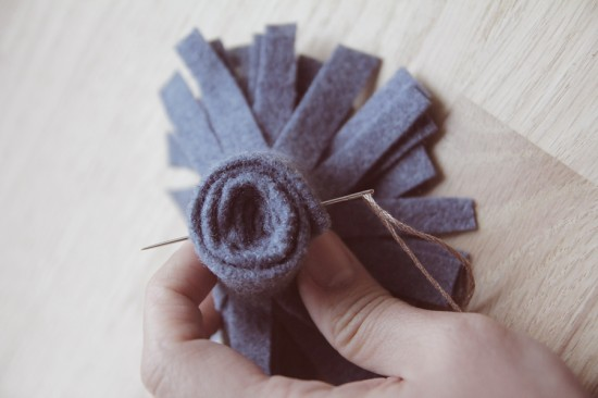 Making felt flowers with a needle and thread in felt strips