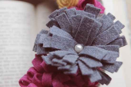 Closeup for finished felt flower, in grey with pearl center.