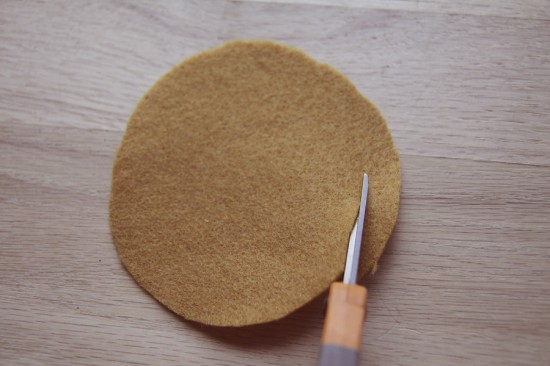 Cutting felt circle to make a felt flower in yellow.