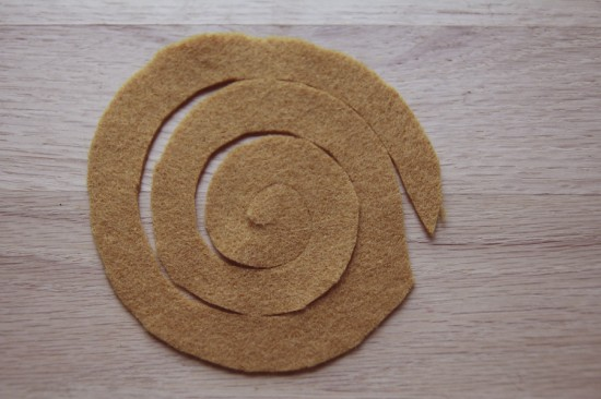 Spiral cut felt circle for felt flower project, in mustard yellow.