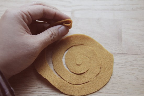 Rolling up felt swirl to make a felt flower.