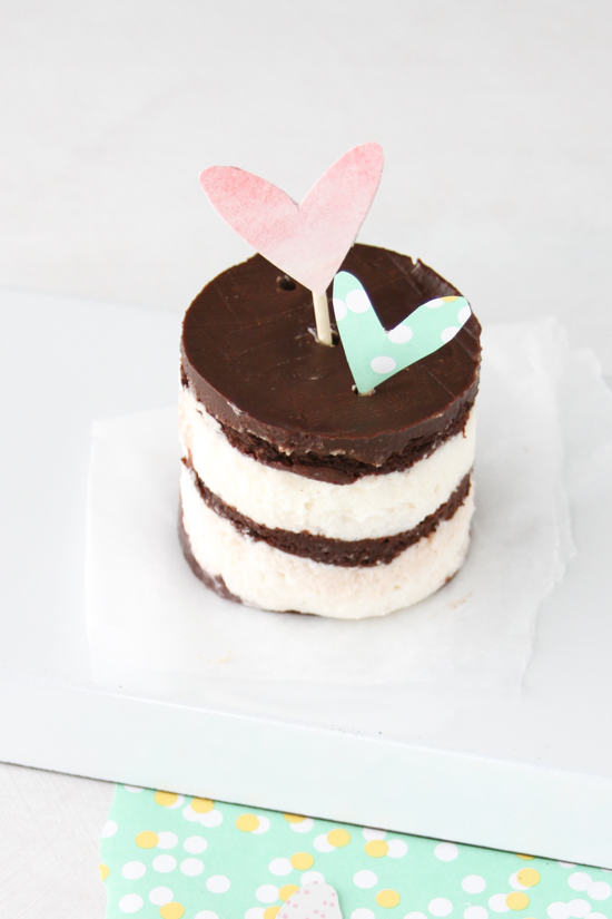 A tiny cake with heart toppers